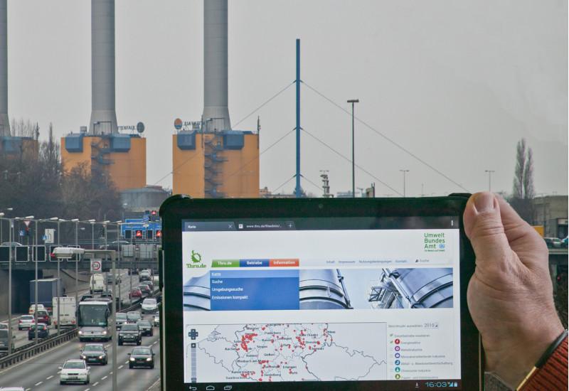Vor einem Energiekraftwerk hält eine Hand einen Tablet-PC hoch. Auf dem Display sind Informationen zu diesem Kraftwerk zu sehen.