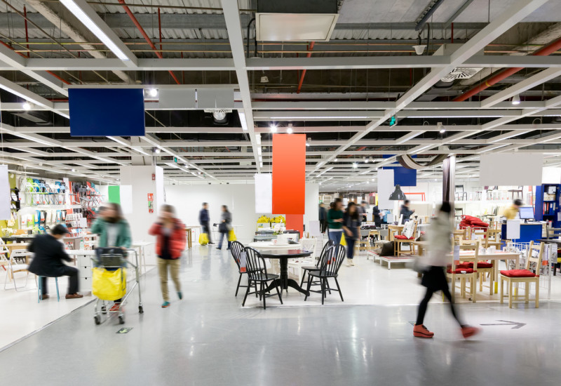 Ein Kaufhaus: Im verschwommenen Hintergrund kaufen mehrere Personen verschiedenene Produkte ein.