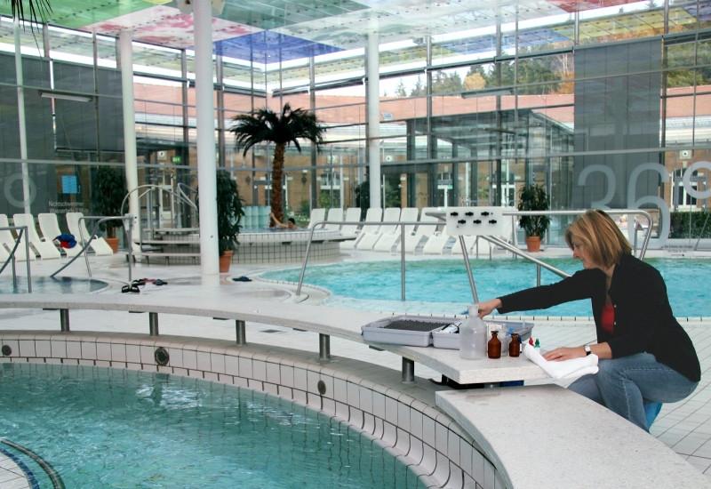Eine Frau entnimmt in einem öffentlichen Hallenbad eine Wasserprobe aus einem Schwimmbecken.