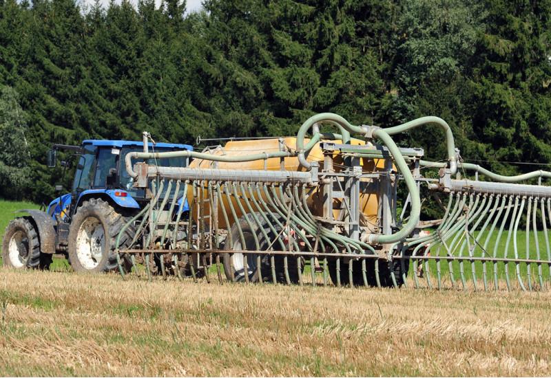 Ein Traktor bringt Gülle auf einem Feld aus. Dafür nutzt er einen Aufsatz mit sogenannten Schleppschläuchen, die dafür sorgen, dass die Gülle nah über dem Boden ausgebracht wird.