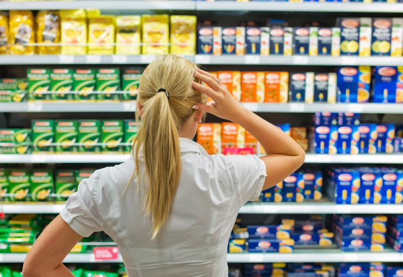 Eine Frau steht ratlos vor einem Einkaufsregal