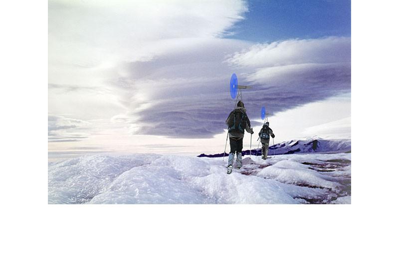 Zwei Bergsteiger laufen auf Schneeschuhen durch eine Eislandschaft, auf dem Rücktragen tragen sie mobile Windräder und erzeugen Strom