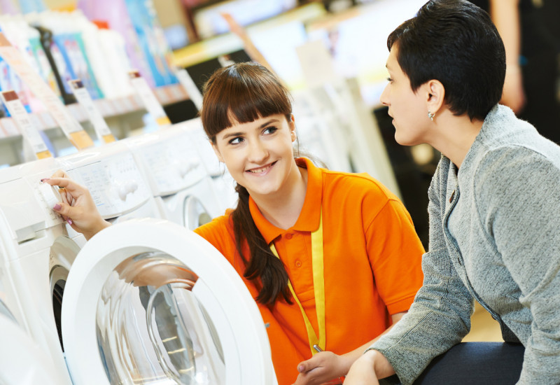 Two women in front of a washing machine