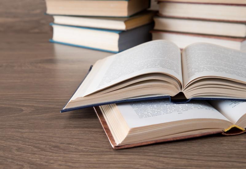Zwei aufgeschlagene Bücher im Vordergrund, im Hintergrund zwei Bücherstapel