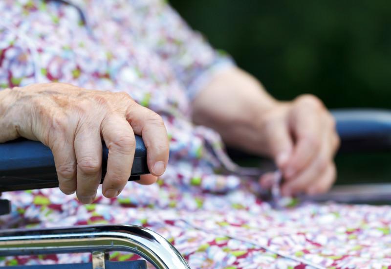 alte Frau sitzt im Rollstuhl