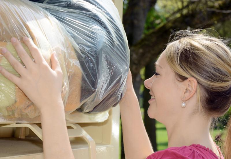 Frau wirft Altkleider in einen Altkleidercontainer