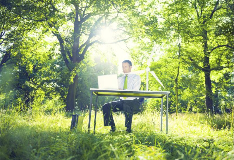 ein Mann sitzt im Freien am Scheibtisch