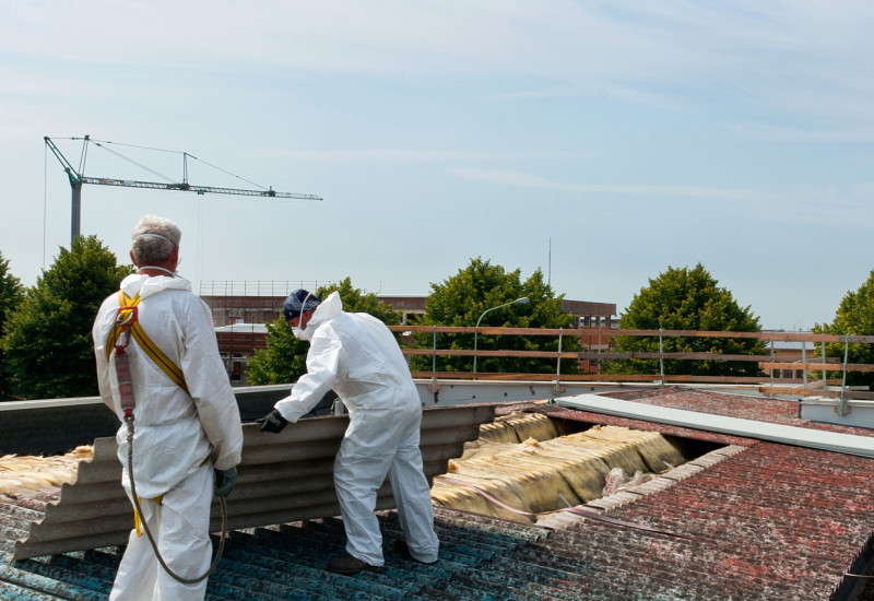 Workers remove asbestos roof sheets