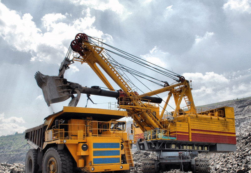 LKW und Bagger beim Abbau abiotischer Rohstoffe