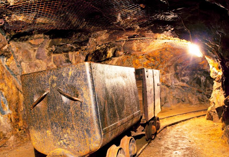 Blick in einen Untertagestollen mit Transportlore auf Schienen
