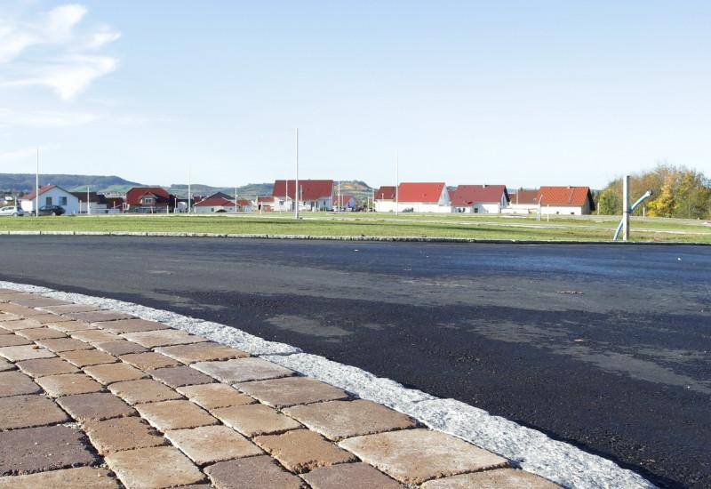 Straße mit Asphalt und Bürgersteig mit Betonpflaster