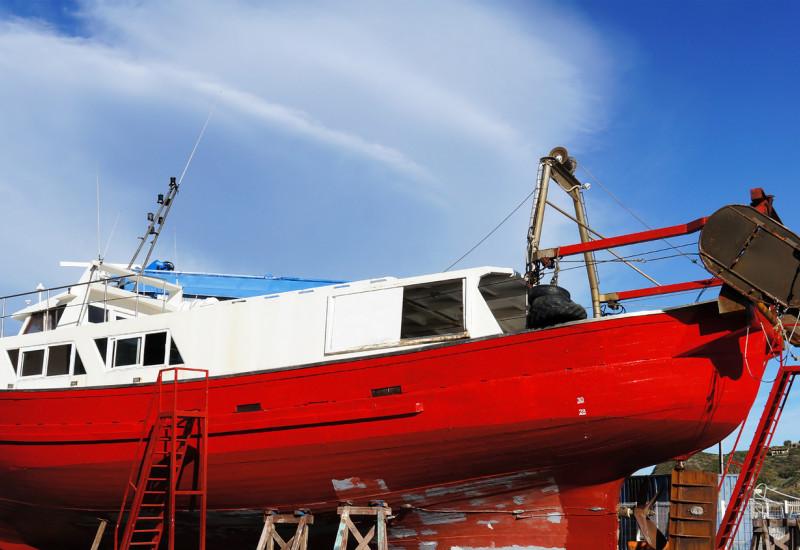 rotes Fischerboot liegt in der Werft, wird neu angestrichen