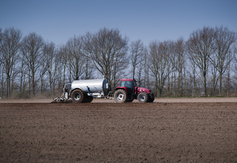 a tractor with trailer spreads slurry on a field
