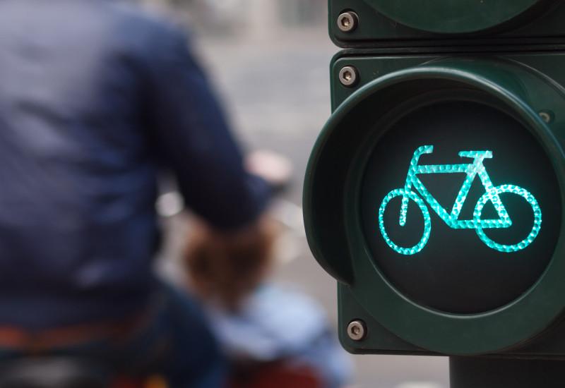 Fahrradampel steht auf Grün, Mann mit gelbem Rad ist vorbeigefahren