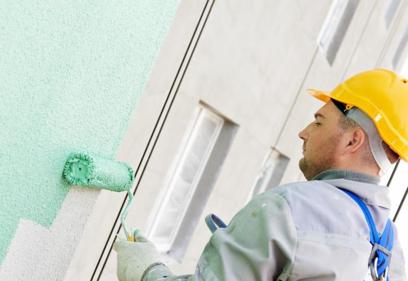Arbeiter streicht Hausfassade grün an