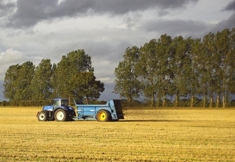 Traktor mit Anhänger auf abgeernetem Feld