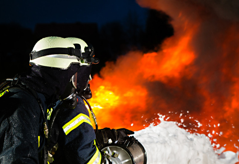 Ein Feuerwehrmann hält den Schlauch, aus dem Schaumlöschmittel quillt, im Hintergrund ist Feuer