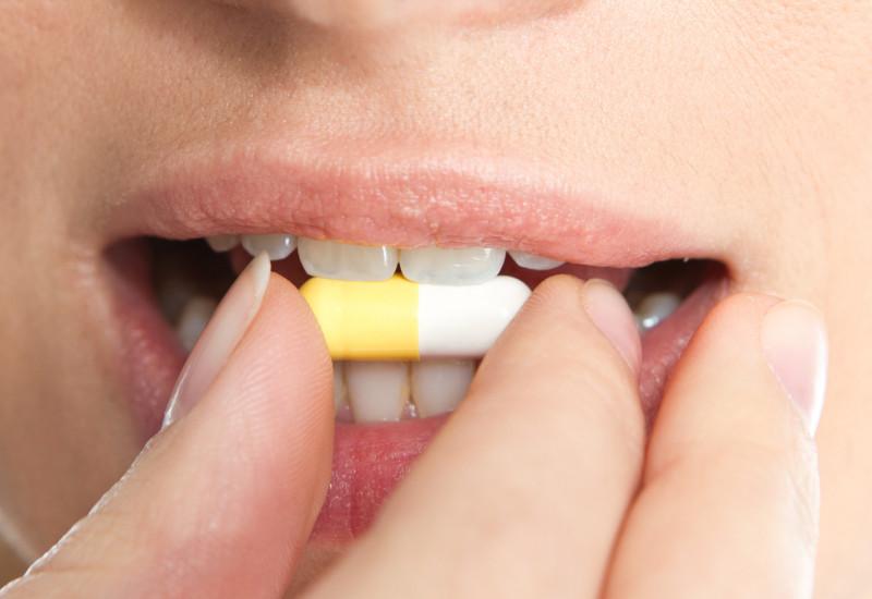 Das Bild zeigt den Mund einer Frau. Mit ihrer rechten Hand führt sie eine Tablette an ihren Mund.