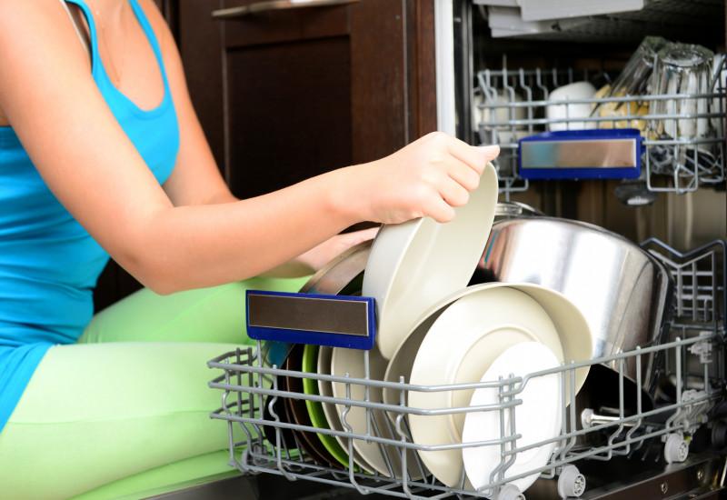 Frau räumt Spülmaschine ein