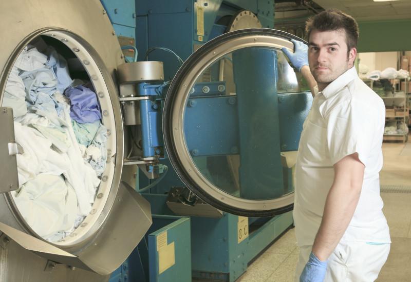 Mann vor Industriewaschmaschine