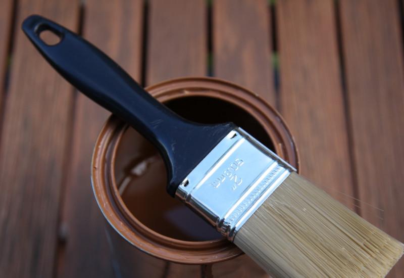 Holzschutz-Farbdose mit brauner Farbe mit einem quer darüber liegenden Pinsel