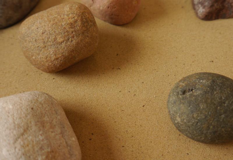 Steine liegen auf hellem Sand.