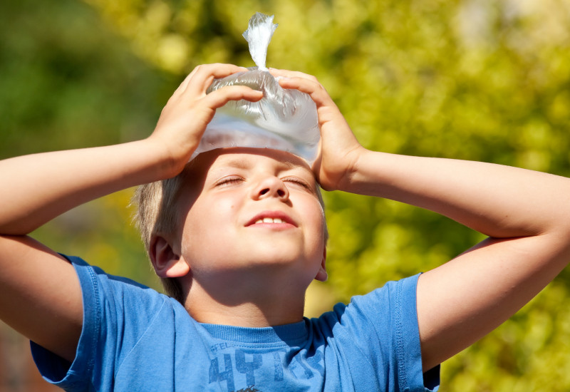 Ein Kind im T-Shirt kühlt sich mit einem Wasserbeutel die Stirn, es ist Sommer.