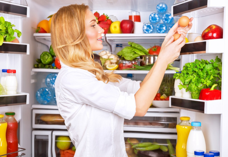 Frau vor offenem Kühlschrank