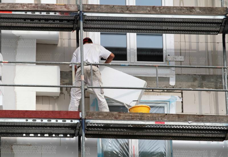 Bauarbeiter dämmen ein Haus