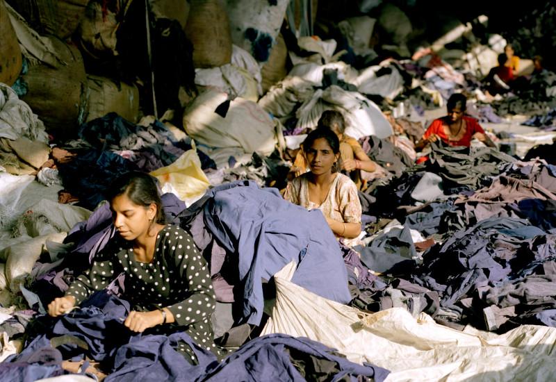 Frauen zerschneiden Jacken und Oberteile; die eingenähten Etiketten werden herausgeschnitten - Marken und Labelsangaben werden bei dem Prozess wertlos.