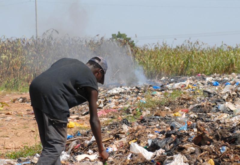 Ein Mann wühlt im brennenden Abfall