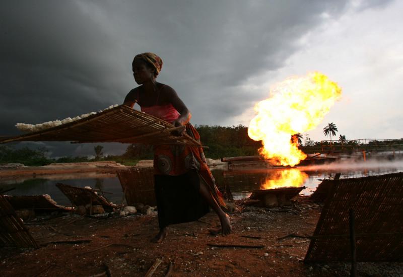 Afrikanische Frau arbeitet am Wasser, Feuer im Hintergrund