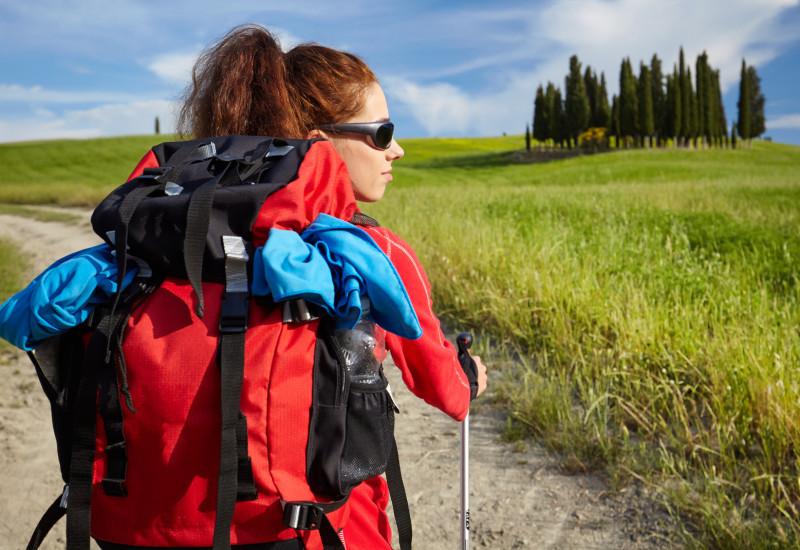 Frau mit Outdoorjacke und Rucksack beim Wandern