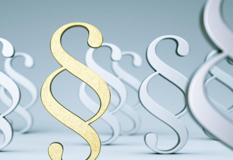 goldenes Paragraphenzeichen umgeben von grauen und weißen Paragraphenzeichen