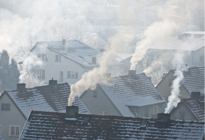 different houses, covered with snow, with smoking chimneys