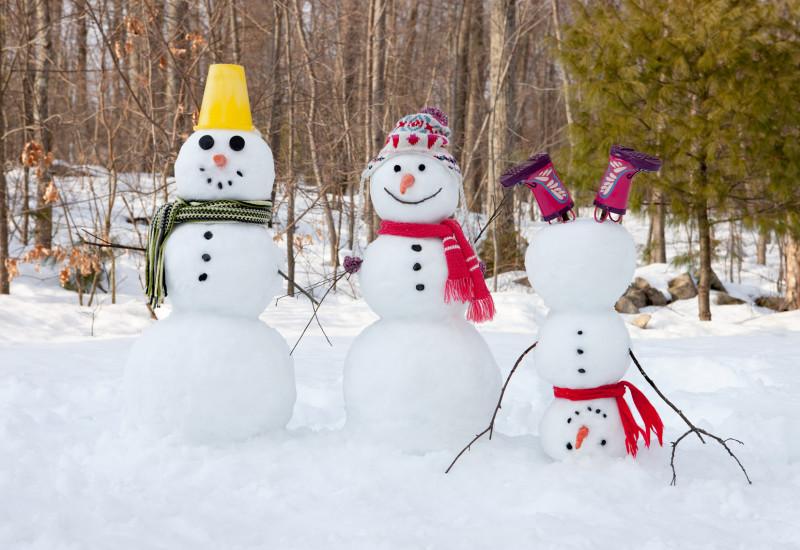 Drei Schneemänner mit Hut und Schal. Einer steht auf dem Kopf und trägt Gummistiefel