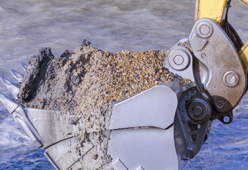 Excavator bucket with sediment in a river