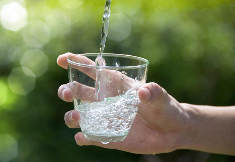 Wasserstrahl trifft von einer Hand gehaltenes Wasserglas
