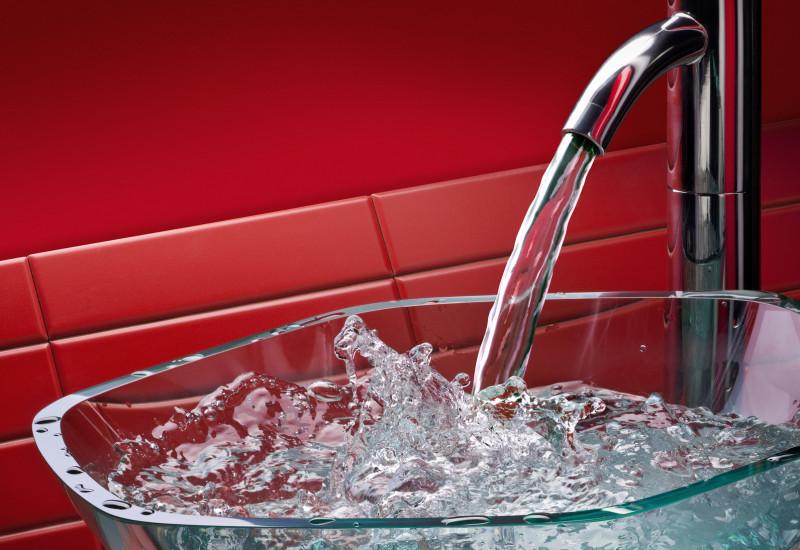 Trinkwasser fließt aus einem Wasserhahn in ein Becken aus Glas