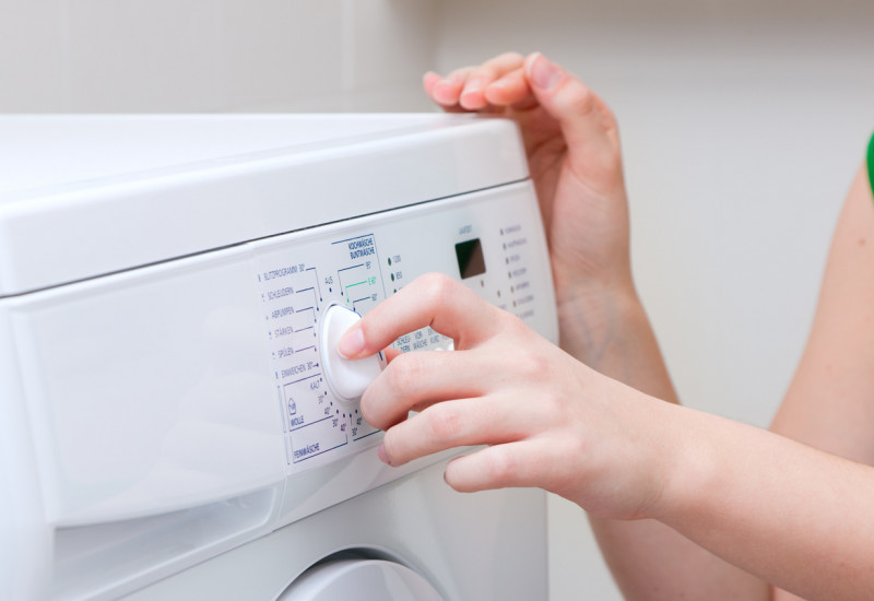 Eine Frau dreht am Programmwählknopf einer Waschmaschine.