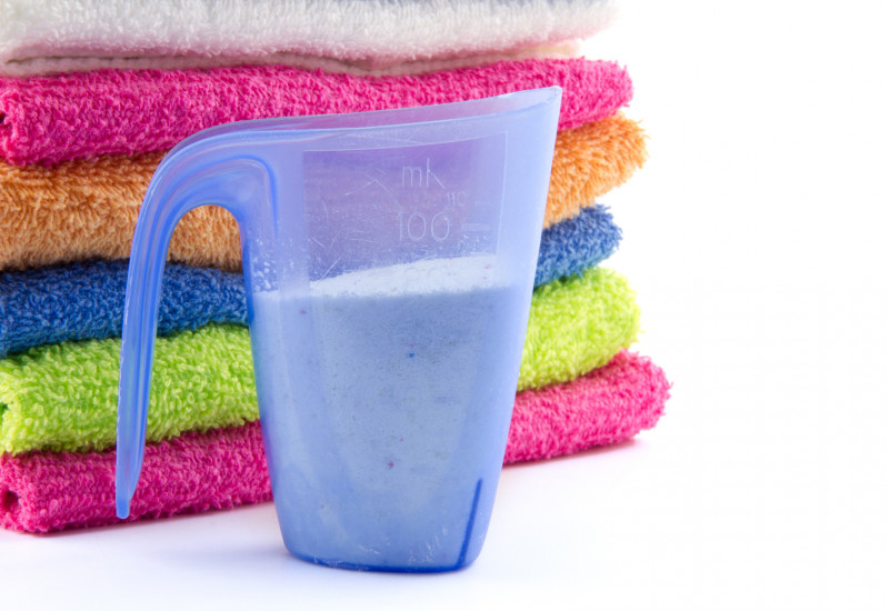 Dosierbecher für Waschmittel vor bunten Handtüchern