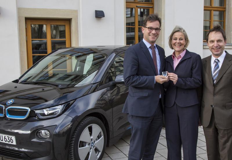Der Parlamentarische Staatssekretär des BMUB, Florian Pronold, bekommt von Nicola Bruening und Marco Schulz vom BMW Vertrieb ein Elektroauto von BMW übergeben.