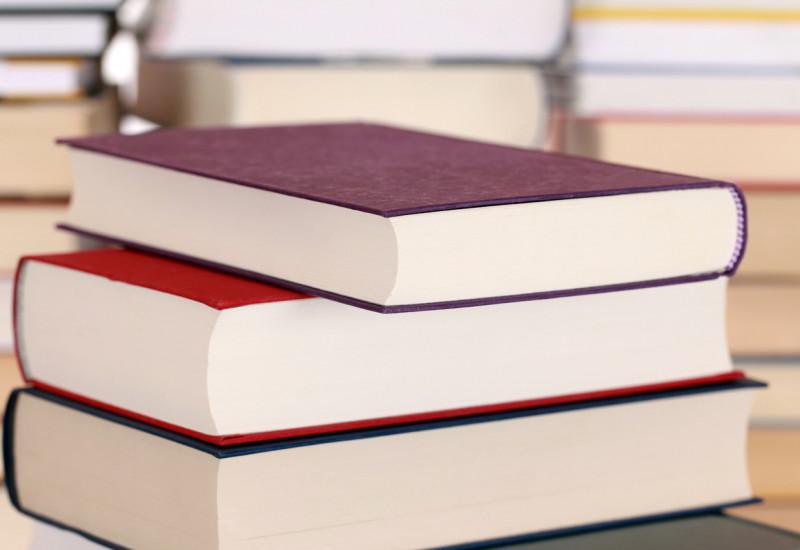 Stapel mit Büchern, die farbige Einbände tragen.