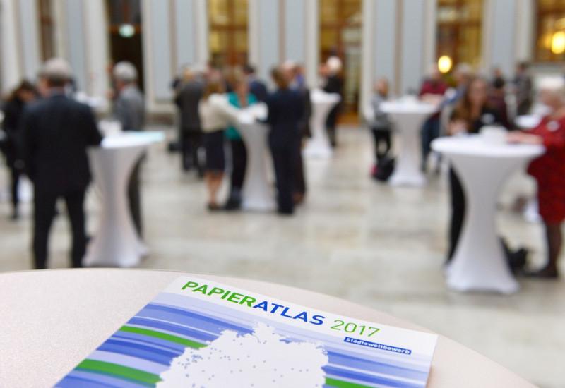 Im Hintergrund Menschen an Stehtischen, im Vordergrund liegt eine Broschüre zum Papieratlas 2017 auf einem Stehtisch