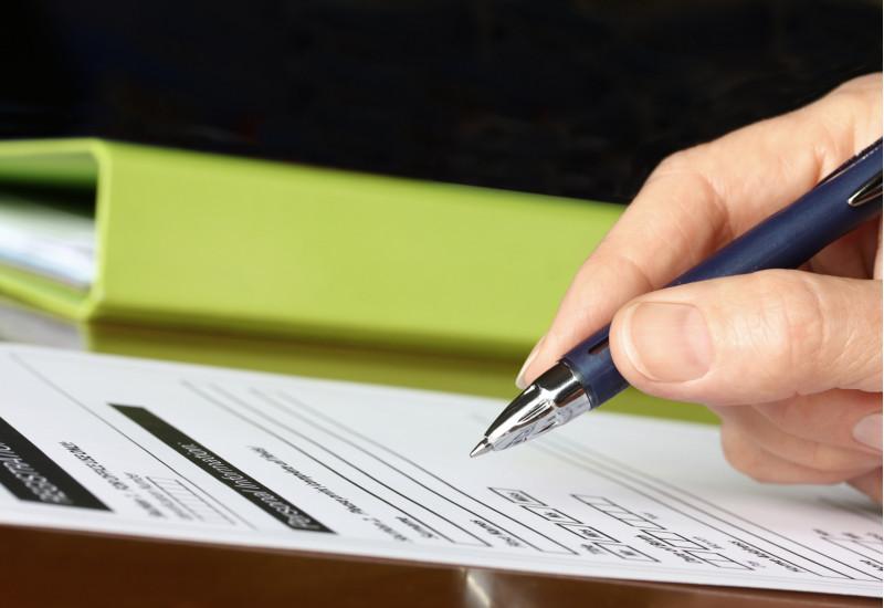 Im Vordergrund Hand hält Stift vor einem Blatt Papier. Im Hintergrund ein grüner Ordner.