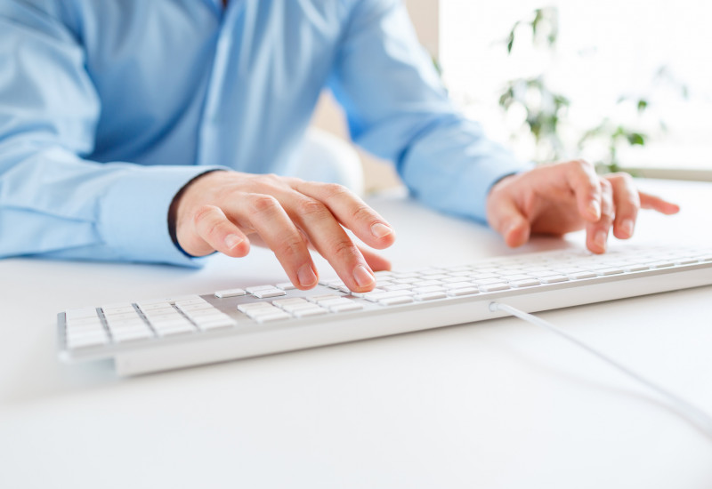 Ein Mann tippt auf die Tastatur.