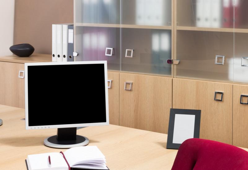 ein Schreibtisch mit Computer, dahinter Büroschränke