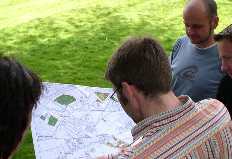 Rückenansicht von vier Personen, die gemeinsam einen Plan betrachten.