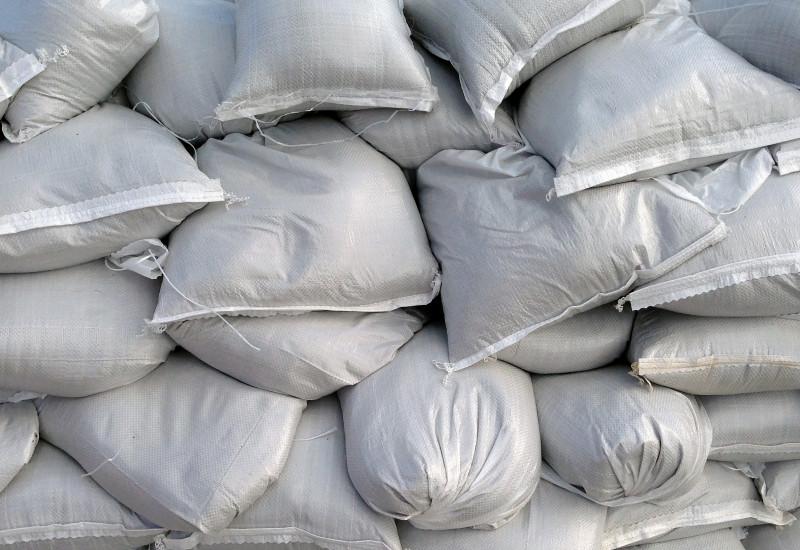 Großaufnahme gestapelter Sandsäcke aus silberfarbenem Kunststoffgewebe.