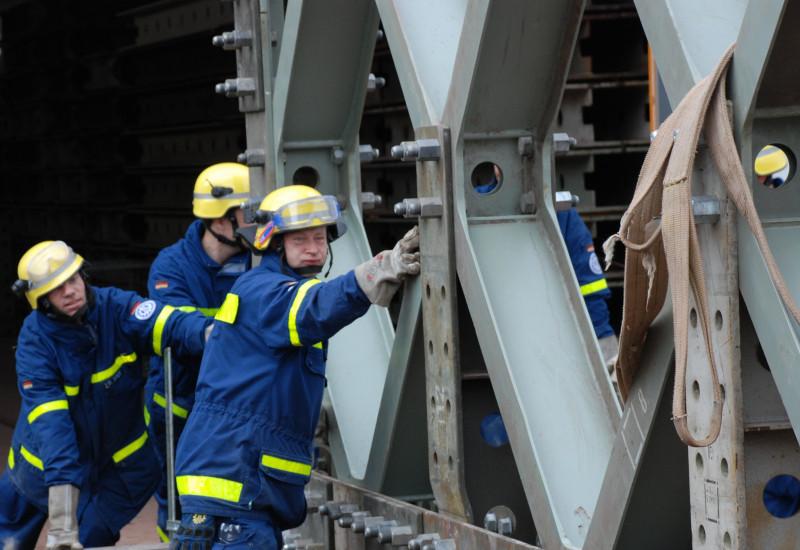 Einsatzkräfte des THW schieben eine große Stahlkonstuktion.